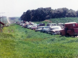 #259=Cars along road on day of farm sale; July 27, 1967