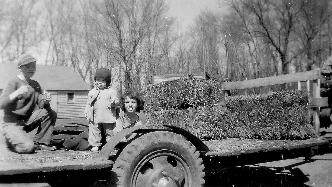 #45=Elliott, Lowell & Rosie on hay wagon(March 1955)